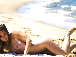 Petite setting up MILF Lily Chey suntanning not susceptible the beach